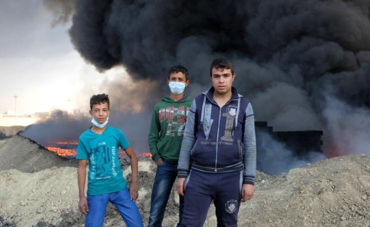 Children near an oil fire at Qayyarah, where ISIS blew up 16 well heads, 26th October 2016. Photo: Benedetta Argentieri / Oxfam.