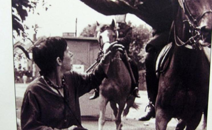At the Orgreave Colliery in 1984, a mounted policeman takes a swing with his baton at Lesley Boulton of Women Sgainst Pit Closures. Photo of newspaper cutting by Diego Sideburns via Flickr (CC BY-NC-ND).