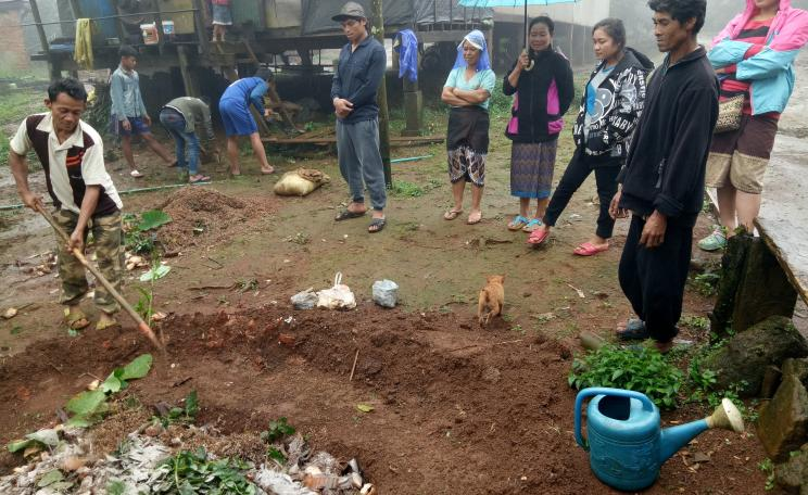 Chon hoes compost for his coffee crop as his family look on.