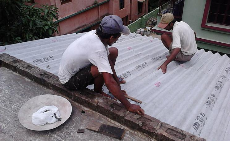 A corrugated asbestos roof is installed on a roof in India. The low cost material is still used regularly in developing countries (c) Biswarup Ganguly