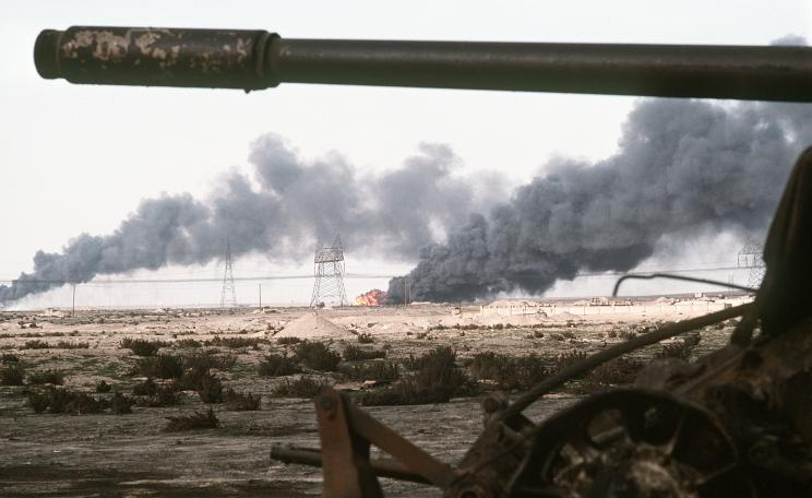 A Kuwaiti oil field set afire by retreating Iraqi troops burns in the distance beyond an abandoned Iraqi T-55A tank following Operation Desert Storm.