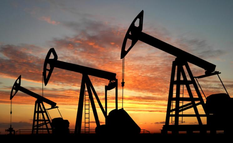 Silhouette of oil pumpjacks in a setting sun