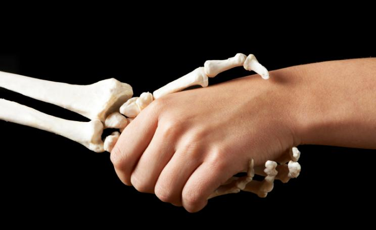 A skeletal hand shakes a fleshly one...