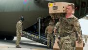 A Royal Marine Commando unloading aid supplies from a RAF C-130.
