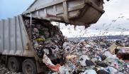 A rubbish truck dumps waste at a landfill site