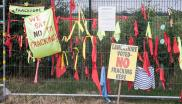 Placards and ribbons on a fence at an anti-fracking protest