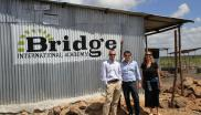 3 people standing outside a Bridge International Schools building