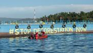 "Greenpeace activists paint ""Stop Deforestation Now"" onto the hull of a  tanker at the Wilmar International refinery in Bitung, North Sulawesi."