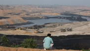 A man stands on the edge of the PKEB minning site that was earlier his village land in Ghatbarra