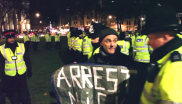 A policeman approaches Donnachadh McCarthy to arrest him in the middle of a media interview in Parliament Square, 19th December 2014. Photo: still from Youtube video by letmelooktv (embedded below).