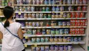 A woman shopping for infant formula at a supermarket in Singapore scans the many different varieties on offer.