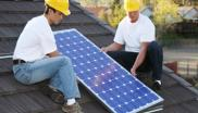 Workmen install a solar panel on a roof